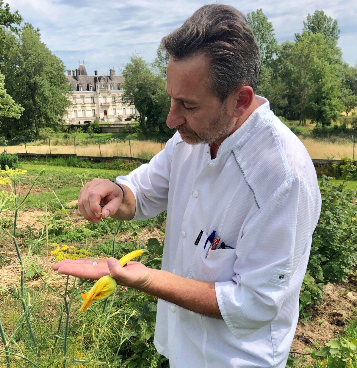 Pascal Pressac dans son potager avec le chateau de Nieuil au fond