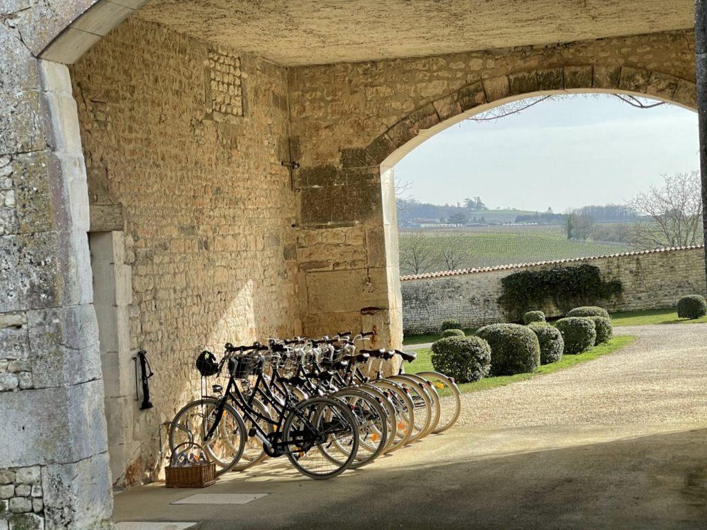 vélos sous le porche du Logis du Frêne et vue sur la campagne environnante