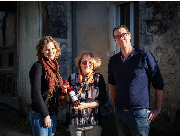 cognac L'esprit de famille. Bernadette tenant dans ses mains une bouteille du Cognac de Bernadette élaborée par Jean Pasquet et son épouse Amy, entourant Bernadette.